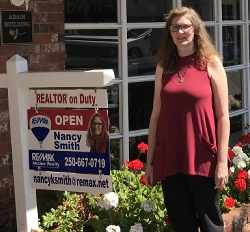 Photo of Nancy Smith beside for sale sign